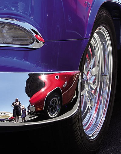 Joshua Tipton is reflected in a '55 Chevrolet Bel Air along with Elly, 2, and Aden, 5, as they look at cars Saturday. (JC AMBERLYN/Miner)