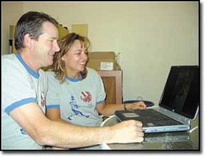 Miner Photo/TERRY ORGAN Mike and Regina Cobb view pictures on a laptop computer of her recent trip to Hanoi, Vietnam. Regina is a dentist who volunteers her time for Resources Exchange International.