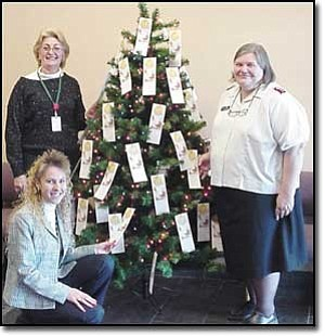 Courtesy Photo Capt. Susan Spousta, right, of the Salvation Army finishes adding angels to the Mohave County Sheriff¹s Office Angel Tree. Department employees selecting their angels are Administrative Assistant Michelle Curtis, kneeling, and Civil Division Senior Office Assistant Cindy Desilets.