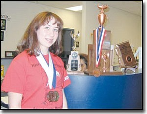 TERRY ORGAN/Miner<br> Kingman Academy of Learning High School junior Brooke Adams wears the medals she received in an Academic Decathlon competition held Feb. 3-4 at Snowflake High School. Resting atop the counter beside her are symbols of honors earned by the school's Academic Decathlon team at the event.