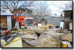 JC AMBERLYN/Miner The Kingman Police Department's Neighborhood Services cleaned up a property in the 2300 block of Phoenix Avenue on Wednesday that contained two abandoned tow trucks among other auto parts, broken furniture and metal scraps.