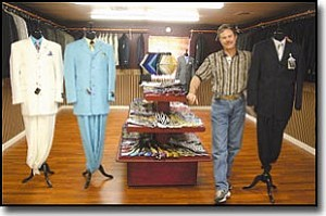 JC AMBERLYN/Miner<br> Kelly Fallis stands by some of the men's suits and ties that will be available for sale at the new men's fine clothing store. Pictured are Stacy Adams suits on the left and a Giorgio Cosani suit on the right.