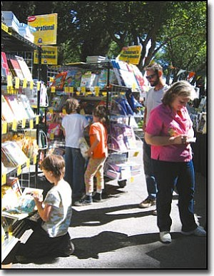 AIBING GUO/Miner<br> David Despain looks on while his three kids (from left) Emma, Sarah and Becca check out children's books Saturday at the KABAM festival. His wife, Linda Marie, works on a book-purchasing list.