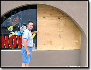LORIN McLAIN/Miner<br> R.A.W. Sports owner Mike Cobb stands by a window broken by burglars on both Thursday and Friday nights.