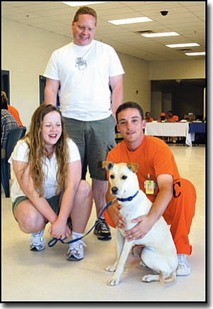 JC AMBERLYN/Miner<br> Lady 2 is one of three dogs that graduated from a dog-training program at Arizona State Prison-Kingman on Friday. Here, she sits with her new adoptive owners and the inmate trainer who spent the last six weeks working with her.