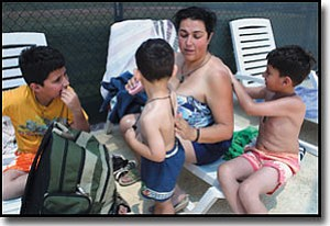 JC AMBERLYN/Miner<br> Cristina Neira-Weston and her children, from left to right,  Christian, Maximus and Enmanuel, put on sunscreen Wednesday morning at Centennial Park Pool.