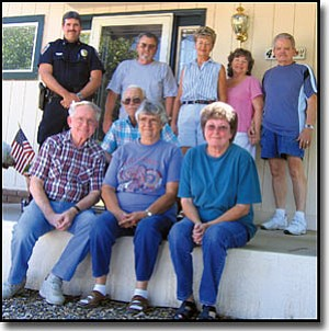 AIBING GUO/Miner<br> Back row from left, KPD Patrol Captain Scott Wright and Neighborhood Watch members Dave Dunlap, Andrea Ohlemann, Pam and Jerry Fink, James Chapman, and front row from left, Bill Patchen, Mona Chapman and Karen Dunlap gather in front of Bill Patchen's house on Christy Drive.