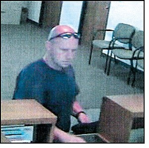 This suspect is wanted for allegedly robbing a Kingman savings and loan on July 31. He is pictured during a robbery July 28 at a bank in St. George, Utah.