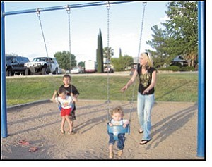 Jennifer Stremel pushes her 17-month-old son, Gauge Peeler, while he watches his cousins swinging at left. Quentin Lopez, 8, is trying to get his brother, Tristin, 4, going during a recent family outing at Cecil Davis Park.