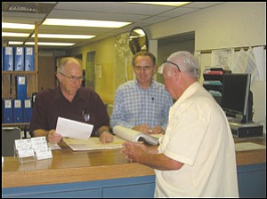 From right to left, Engineering Technician Senior Derle Walker and Engineering Technician Senior Jerry Williams help Jim Shipman with Kingman Town and Country Realty learn the flood zones for a piece of Mohave County property. Both Walker and Williams work within the Flood Control Division of the Mohave County Public Works Department.