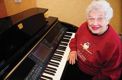 Les Stukenberg/The Daily Courier<br> JoAn Ramsay poses with the baby grand piano at her Prescott residence Wednesday morning.
