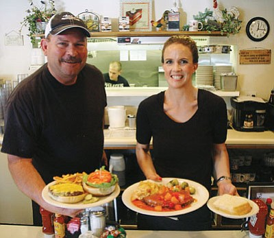 Deano's Sweet Potato Café owner Dean Herbert holds a cheeseburger and fries, while Jessica Morgan displays the Prescott café's baked ham special, covered in a pink champagne sauce, which comes with scalloped potatoes and fresh vegetables.<br /><br /><!-- 1upcrlf2 --><br /><br /><!-- 1upcrlf2 -->Patrick Whitehurst/The Daily Courier