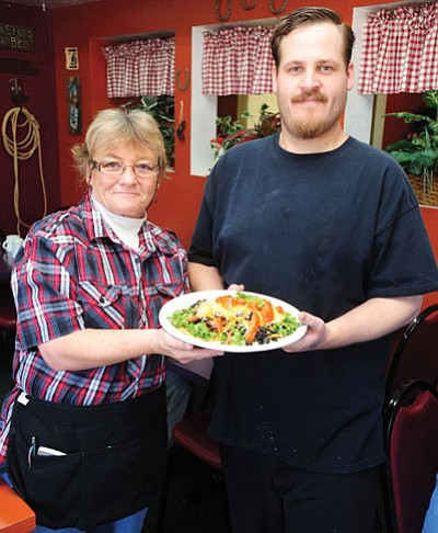 Les Stukenberg/The Daily Courier<br> Waitress Melaney Ross and cook Matthew Boyer hold a plate of tostadas from the Cowgirl in the Kitchen Café on Commerce Drive in Prescott.