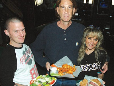 Patrick Whitehurst/The Daily Courier<br> From left, Pudge & Asti's cook and bartender  Kyle Fraser and owners Craig and Suzy Denny  hold some of the sports  bar and grill's customer favorites – a Greek salad, grilled hot wings, and  Kirk's Chainsaw sandwich.