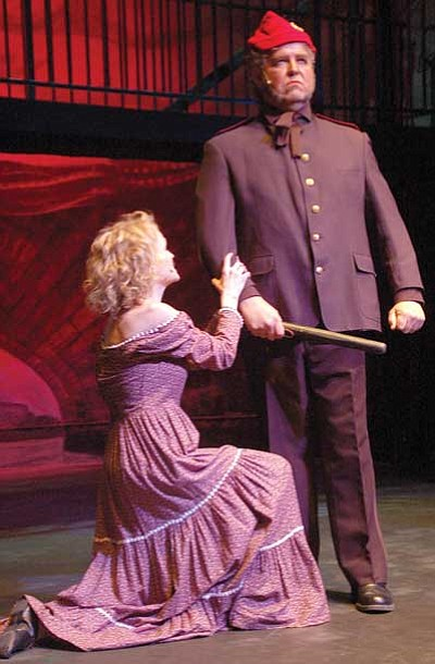 "Below, Fantine (Gina Steverson) pleads with Officer Javert (Philip Dixon), insisting she's not a prostitute in PCA's production of the musical play ""Les Misérables."""