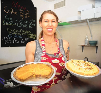 Owner and head cook Kim Pinker holds a coconut pie and a vanilla carmel pie at the Rustic Pie Co. on Valley Street.  Below left is a strawberry pie, and below right is the mixed berry pie.<br> Les Stukenberg/The Daily Courier