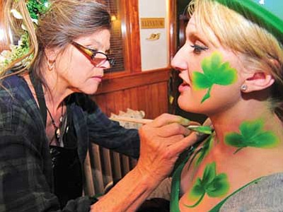 Les Stukenberg/The Daily Courier, file<br> Mary Anne paints shamrocks on Kate Kinchen outside of the Jersey Lilly Saloon during the 2014 St. Patrick's Day Pub Crawl in downtown Prescott.