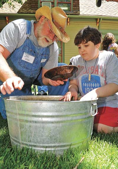 Sharlot Hall volunteer Bob Dennis shows Daniel Chaffin, visiting Prescott from Oregon, how to pan for gold. (Matt Hinshaw/The Daily Courier, file)