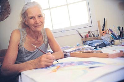 Ananda DiBenedetto works on a watercolor in her Prescott studio. (Les Stukenberg/The Daily Courier)