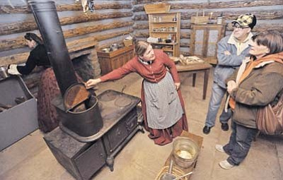 In this file photo, Marion Arrington talks with Jean and Ken Hansen about the 1864 wood burning stove she is using to bake gingersnaps during Sharlot Hall's 2014 Frontier Christmas event in downtown Prescott. (Matt Hinshaw/The Daily Courier, file)