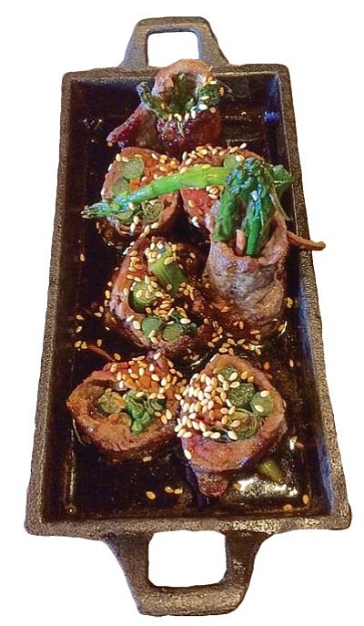 Negimaki, an Augie's appetizer, consists of sliced New York steak cut thin and then flattened and rolled around carrots, scallions, and asparagus. It is grilled and served in a cast iron skillet on a butcher block in a delicious teriyaki sauce covered with sesame seeds.