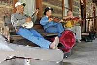 Matt Hinshaw/The Daily Courier<br>John Clabourne, left, and John Beland, middle, members of the Arthritis Brothers String Band from Sierra Vista, AZ jam with their friend Jim Junker on the porch of the Governors Mansion during the 31st Annual Folk Music Festival at Sharlot Hall in 2009.
