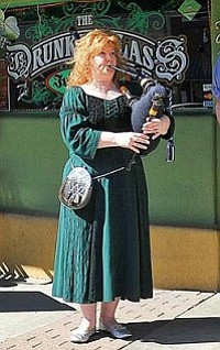 Matt Hinshaw/The Daily Courier<br>Denise Robinson plays a set of bagpipes in front of The Drunken Lass pub during last year's St. Patrick's Day Pub Crawl in downtown Prescott.