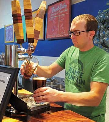 Matt Hinshaw/The Daily Courier<br> Michael Stanger, one of the four owners of Granite Mountain Brewing, pours a pair of craft beers for a waiting patron Friday evening in Prescott.  Granite Mountain Brewing opened its doors on Aug. 8.