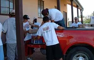 <i>Photo by Jeff Pope</i> <b>Photo courtesy of Docia Blaylock Varsity football players were up early on Aug. 27 to take books from the Winslow Public Library to St. Paul¹s Episcopal Church (above).</b>