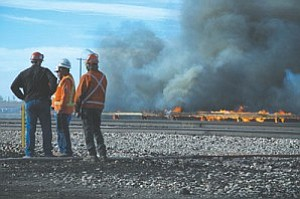 BNSF Railroad workers survey the damage of the bridge as fire crew fight the fire below.