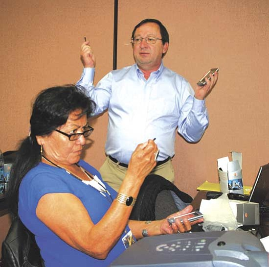 <i>Courtesy photo</i><br> Emma Yoe, a senior community health worker from Chinle works with a PDA while George Purvis of Space Data Corporation explains how to use the monitors during training for supervisors and staff of the Navajo Nation Special Diabetes Project (NNSDP) on Jan. 28.