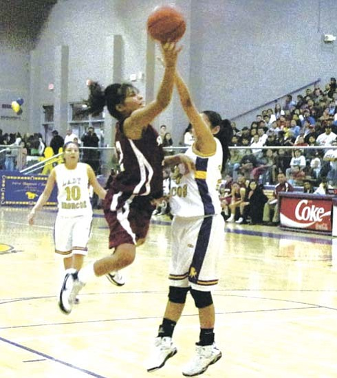 <i>Photo by Anton Wero/NHO</i><br> Tenisha Royston (32) of the Shiprock Lady Chieftains shoots over the outstretched arms of Kirtland's Nikki Ford (24), during the New Mexico 1–4A District championship game. The Kirtland Central Lady Broncos won the game 51 to 50.