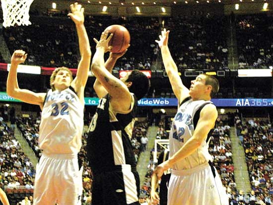 <i>Photo by Anton Wero/NHO</i><br> Chinle's Denzel Harvey (43, center) works for a basket in the paint while Estrella Foothills' Sean Duncan gets ready to block the shot. Estrella Foothills won the 2009 Arizona 3A Boys State Basketball championship game, with a final score of 46 to 40.