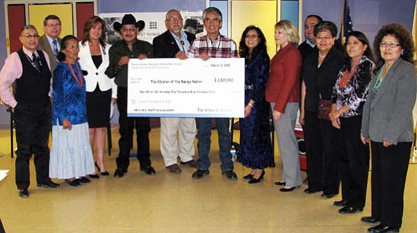 Courtesy photo<br /><br /><!-- 1upcrlf2 -->Navajo Nation President Joe Shirley Jr., and First Lady Vikki Shirley accept a check for $2.6 million from First Things First Chairwoman Nadine Mathis Basha (in red) March 3 at the Karigan Child Care Center in St. Michaels. Over the next 10 years, it is hoped that the Navajo Nation will receive $26 million from the voter-approved program — if the Arizona Legislature does not decide to take the funding to meet the state's budget shortfall. From left to right are Navajo Nation Board of Education member Tim Bitsilly, Bessie Allen, Dr. Paula Curley, Council Delegates Andy Ayze and Larry Anderson, President Shirley, Mrs. Shirley, Mrs. Basha, Spencer Willie, Dorothy Yazzie, Paula Seanez, and Dolly C. Begay. In back (at left) is First Things First Executive Director Elliot Hibbs.