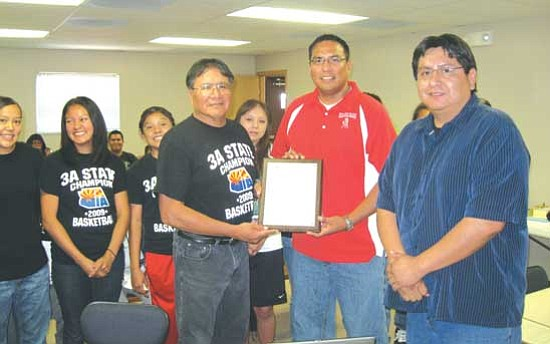 With the help of videoconferencing equipment, Navajo County Supervisor Jonathan Nez (right) recognized the 3A State Champion Monument Valley Lady Mustangs basketball team simultaneously in both Holbrook and Kayenta during the Board of Supervisors meeting on May 26. Pictured from left to right are Coach Robert Nash, Monument Valley High School Athletic Director Jacob Holiday and Supervisor Nez.