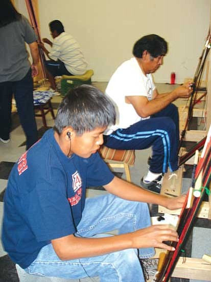 <i>Photo by Rosanda Suetopka Thayer/NHO</i><br> A couple of students work on traditional weavings in master weaver Marvin Pooyouma's Hopi belt-weaving weaving class, which is a part of the Hopitutuquiki art school. Each student learned&#160;how to set up a&#160;traditional loom, design and finish an entire Hopi&#160;men's traditional red-black-green belt within their two week session. Pooyouma is from the village of Hotevilla.