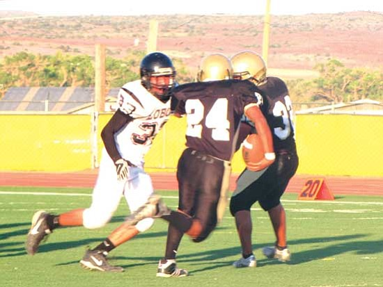 Running back Cody Jones (24) of Chinle goes around the blocking of Stewart Yazzie (32) for a short gain. He was stopped by Austin Anderson (33) of Many Farms.