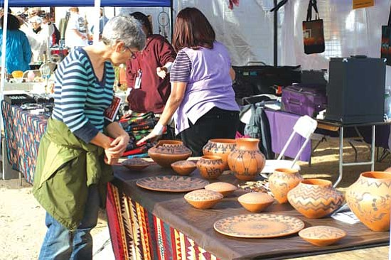 <i>Courtesy photo</i><br> A potential buyer takes a moment to examine some pottery at last year's Pueblo Grande Indian Market.