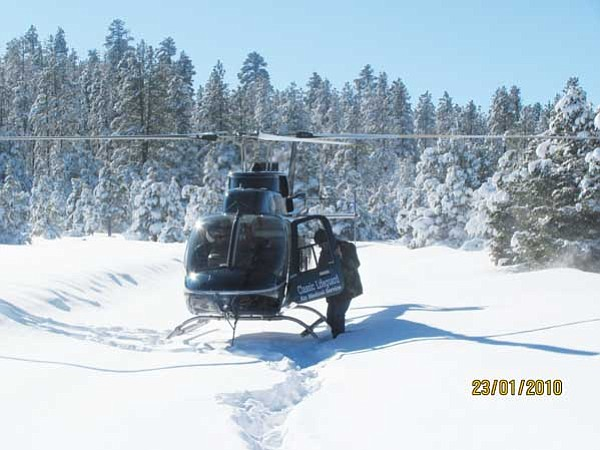 <i>Courtesy photo</i><br> Navajo Nation President Joe Shirley Jr. climbs back into a helicopter during an aerial assessment of the Fort Defiance Plateau on Sunday. Assessments were conducted throughout the Navajo Nation following last week's record snowstorms.