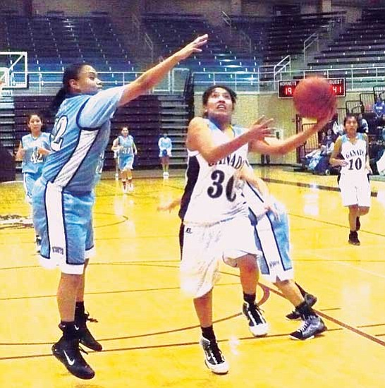 <i>Anton Wero/NHO</i><br> Ganado's Jasmine Taliman (30) drives the paint for two points as she is defended by Window Rock's LaCresha Campbell's (32). The Lady Scouts won an important 3A region win over the Lady Hornets with a final score of 55 to 46.