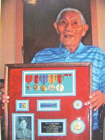 Travis S. Yaiva proudly shows a display case of his medals and honors from his military service.