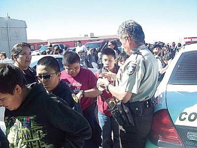 <i>Tyler Tawahongva/NHO</i><br> Coconino County Sheriff's Deputy Robert James hands out stickers to students.