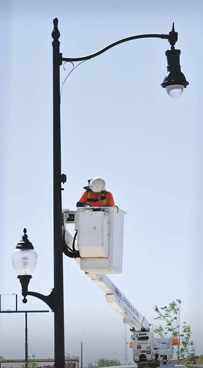 "<i>Todd Roth/NHO</i><br /><br /><!-- 1upcrlf2 -->A worker installs new lighting fixtures in downtown Winslow as part of Phase II of the city's ""Renaissance on Route 66"" beautification project. The new lights are similar to what was used to illuminate the streets of Winslow about 70 years ago, but will utilize metal halide bulbs, which are more energy efficient."