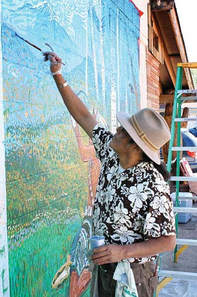 """<i>Ryan Williams/NHO</i><br> Navajo artist Shonto Begay paints scenery on a mural entitled """"Sacred Hunt"""" that was donated to the city of Williams last month. Begay worked on the mural in collaboration with fellow artist Cy Wagoner and an area youth group."""