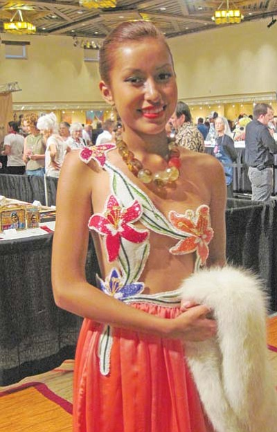"<i>Rosanda Suetopka Thayer</i><br> A young woman smiles as she models a beautiful beaded dress by Orlando Dugi from the ""Beauty and Elegance"" clothing line out of Utah at the 2010 Santa Fe Indian Market. A number of traditional and contemporary types of artistry were honored at this year's Market."
