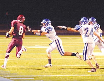 <i>Todd Roth/NHO</i><br> A Winslow Bulldog player runs past several Snowflake defenders during non-regional action last Friday night in Winslow. The Bulldogs were defeated 29-14, but are still 1-0 in the 3A North Region. The Bulldogs will host 3A North rival Ganado Hornets on Friday.