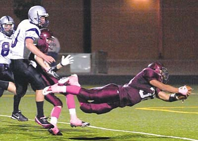 <i>Todd Roth/NHO</i><br> TOUCHDOWN: A Winslow Bulldog player dives in for a score. The Bulldogs, who won 48-0, wore pink in honor of National Breast Cancer Awareness Month.