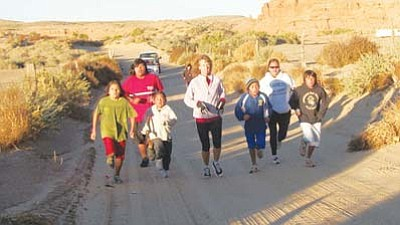 <i>Tyler Tawahongva/NHO</i><br> A number of Hopi students and adults participated in the Red Ribbon Relay, which was held at sunrise on Oct. 28. The relay began in both Spider Mound (east) and Moenkopi (west). The runners eventually met at Hopi Day School in Kykotsmovi where a parade (below) was held to recognize those who continue the fight against drug and alcohol abuse.