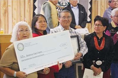 <i>Photo by Laphillda Tso</i><br> From left: Elizabeth Johnson, community services coordinator; Andrea Dawes, office specialist; and Billy Arizona Jr. hold up a check presented by the TCDC and the Navajo Division of Community Development to the Bodaway-Gap Chapter as Navajo Nation Council Delegate Evelyn Acothley looks on.
