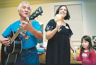 <i>Todd Roth/NHO</i><br> Sidney Poolheco (left) sings a Hopi song with the assistance of April Neil and her daughter on Feb. 11.